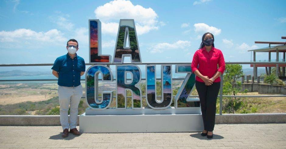 dos personas junto a un letrero que dice La Cruz