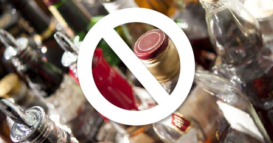 un conjunto de botellas de licor vacías con un signo de prevención pintado sobre ellas