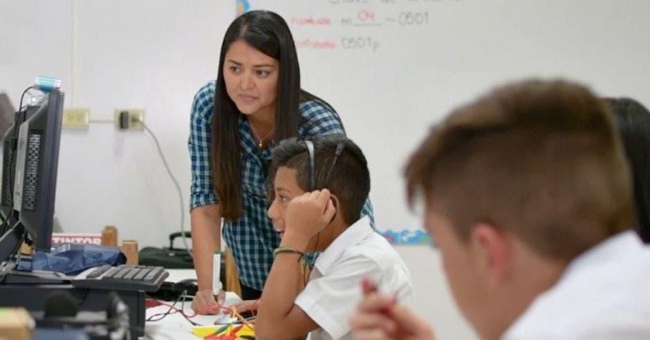 educadora dando clase a niños en salón de cómputo