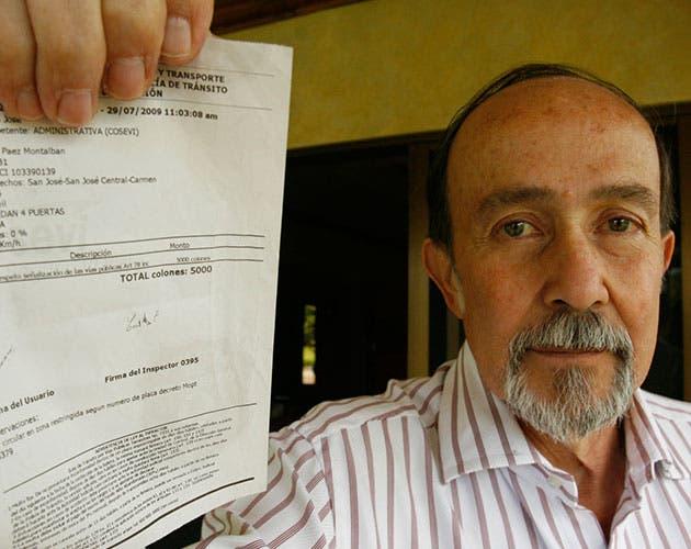 Hombre muestra una multa por restricción en su mano