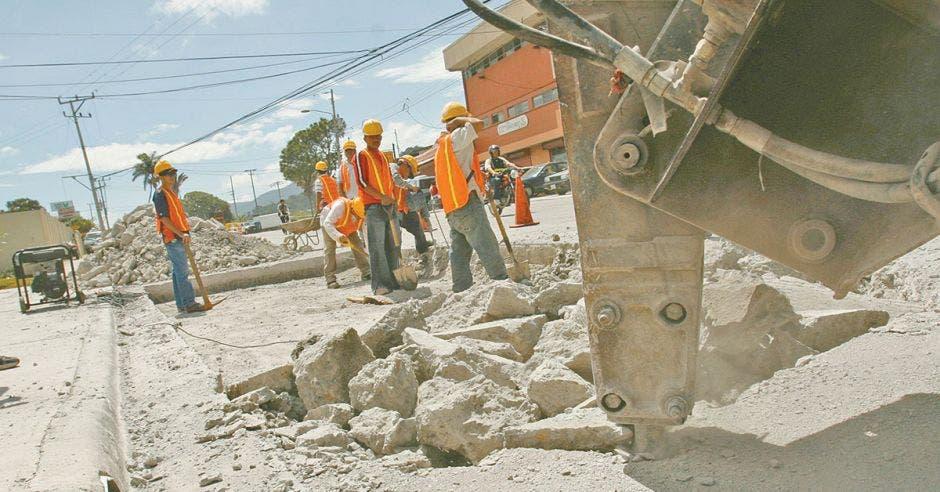 Hombres y maquinaria realizando trabajos de reparación en la carretera