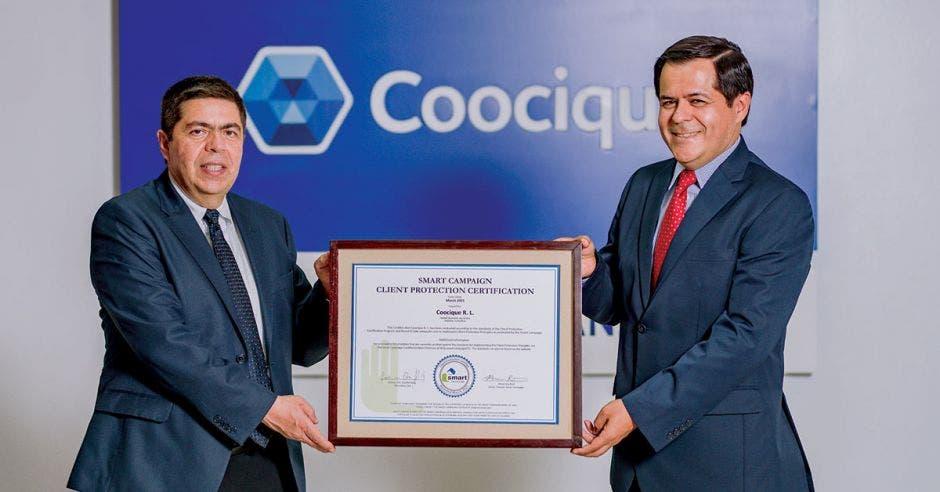 dos hombres de saco y corbata sostienen una certificación de vidrio