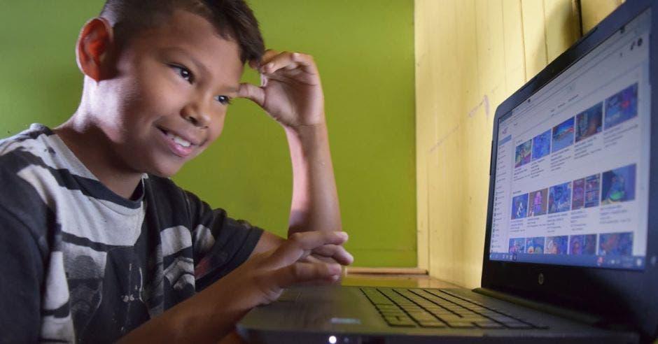 Niño sonriendo frente a una computadora