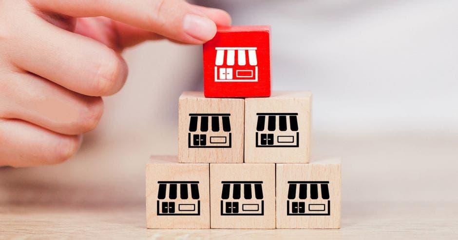 pirámide de cubos de madera con dibujos de franquicia, hasta arriba mano sosteniendo un cubo rojo