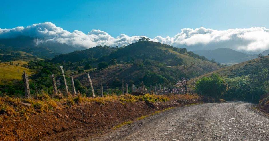 Camino de ripio rural con montañas y volcán de Tenorio (a la izquierda en las nubes) al fondo. Costa Rica
