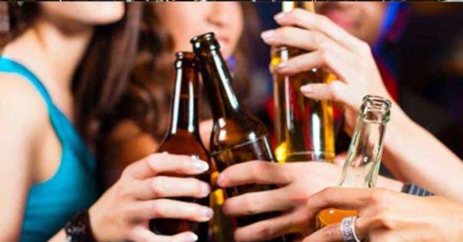 jóvenes brindando con botellas de cerveza