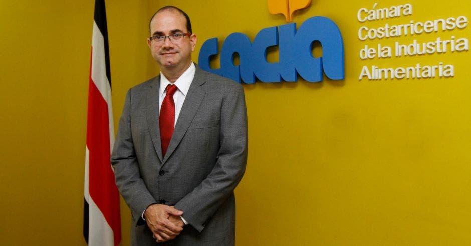 Hombre de traje frente a pared amarilla