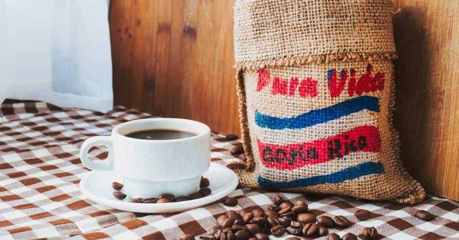 Café costarricense dentro de un saco pintado con la bandera de Costa Rica. Junto al saco, una taza de café negro.