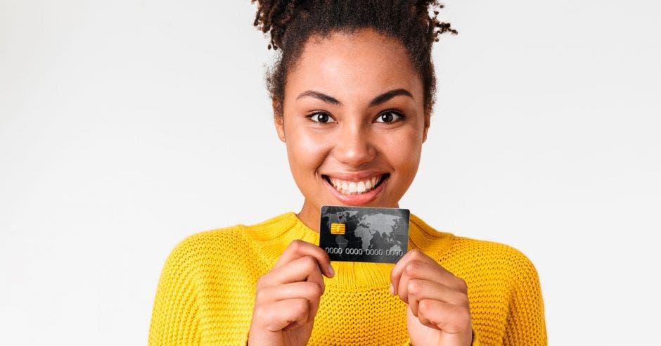mujer sonriendo, con sueter amarillo sosteniendo una tarjeta de débito con las dos manos