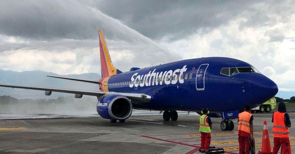 Un avión azul en una pista de aterrizaje