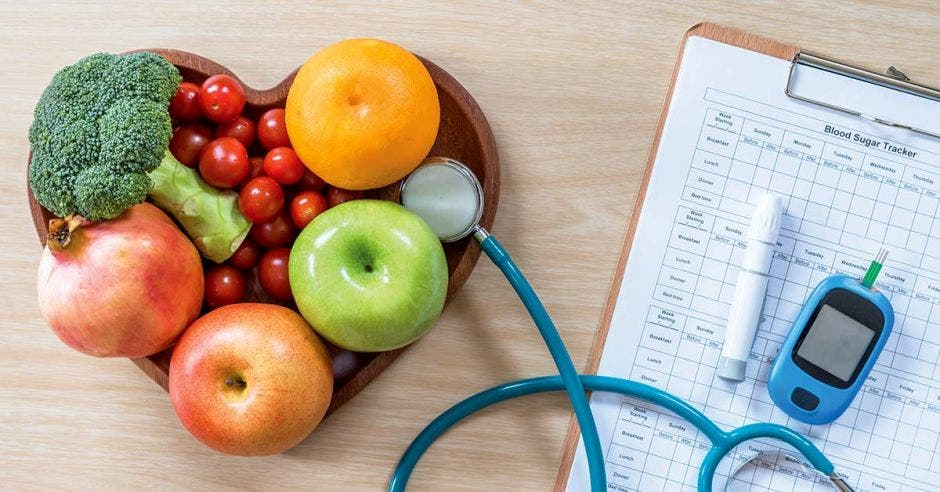 Frutas y verduras y un estetoscopio y herramientas de monitoreo médico