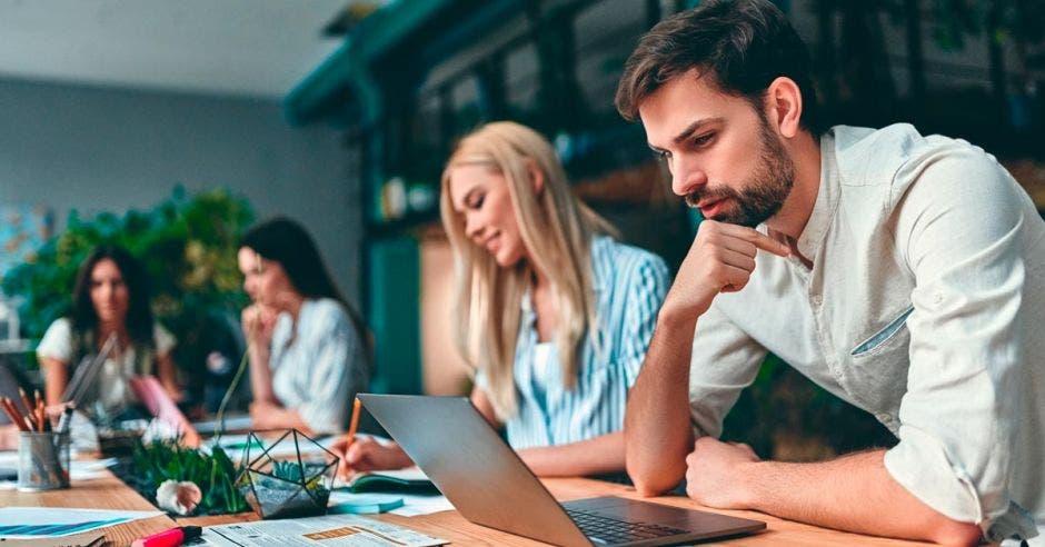 Grupos de jóvenes empresarios trabajan juntos en oficinas modernas. Personas creativas con laptop, tablet, smartphone, portátil.