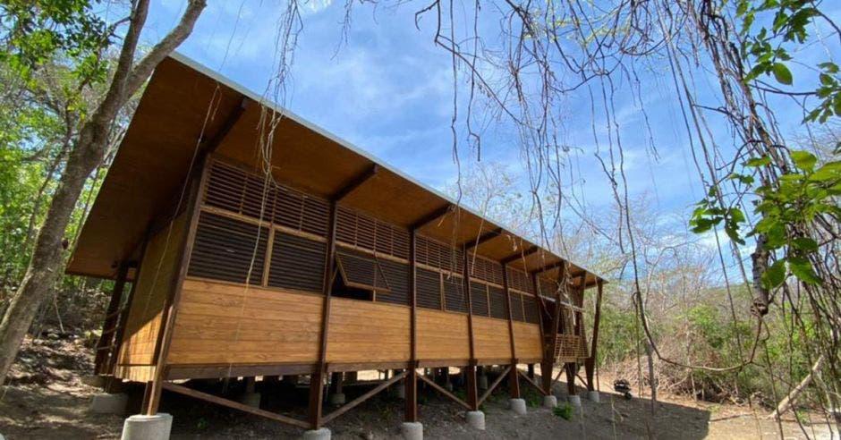 una casa de madera en medio de una bosque seco. La casa está construida sobre pilotes.