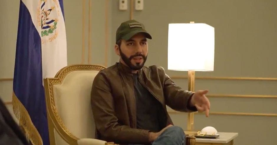 un hombre de gorra verde, barba, chaqueta café, camisa negra y jeans