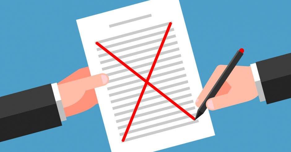 Una mano sostiene el documento, la otra tacha el contenido del texto con un bolígrafo rojo