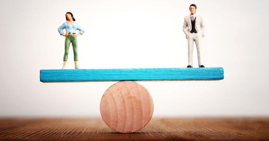 figuras de madera de hombre y mujer sobre tabla azul