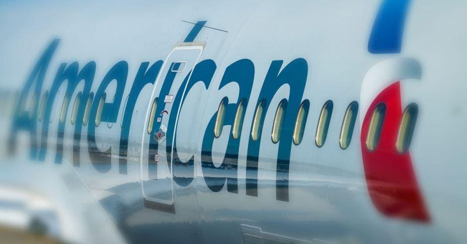 un avión blanco con la marca American en la rampa de una pista de aterizaje
