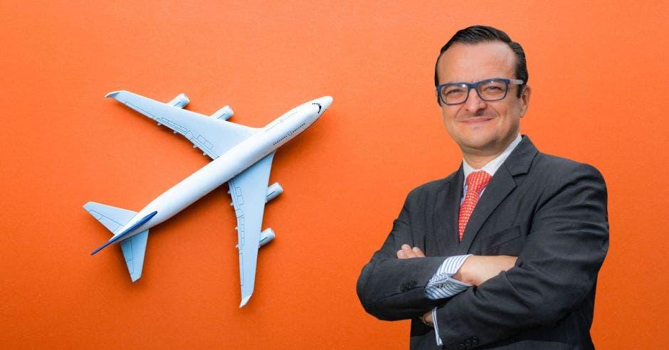 un hombre de traje sobre un fondo anaranjado con un avión blanco