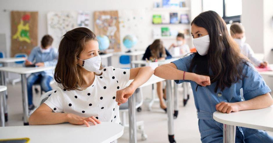 Dos niñas saludándose con el codo