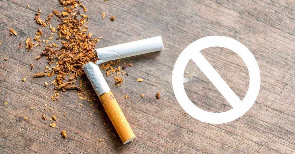 un cigarrillo partido en dos sobre una mesa. Tabaco derramado en la mesa.