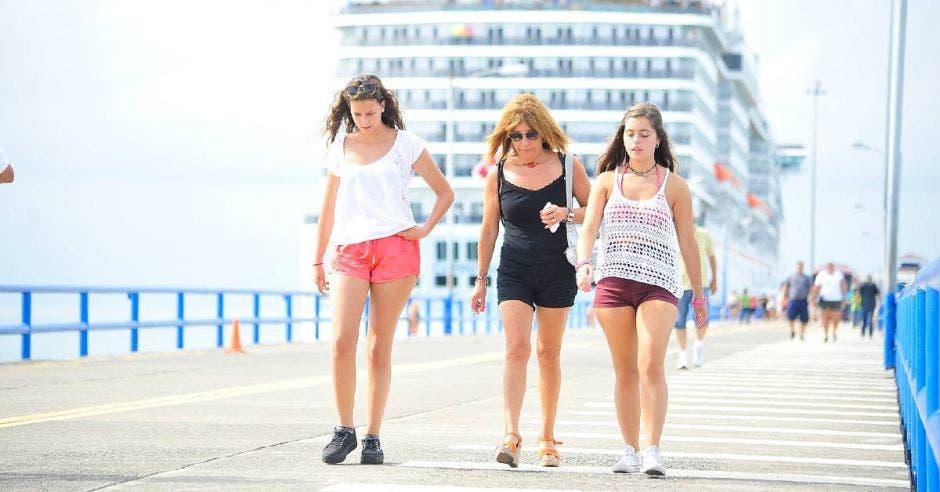 tres mujeres caminan por un puerto. Un crucero encallado en el fondo.