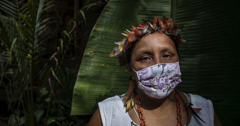 Mujer con mascarilla puesta y planta detrás
