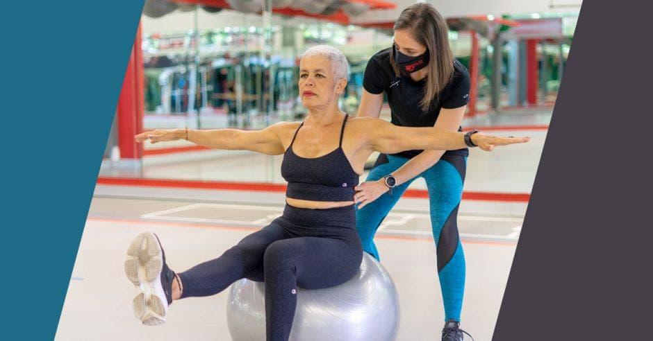 adulta mayor sobre balón ejercicio instructora gimnasio