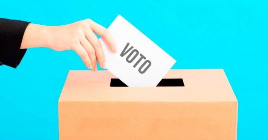 mano depositando papel en urna electoral