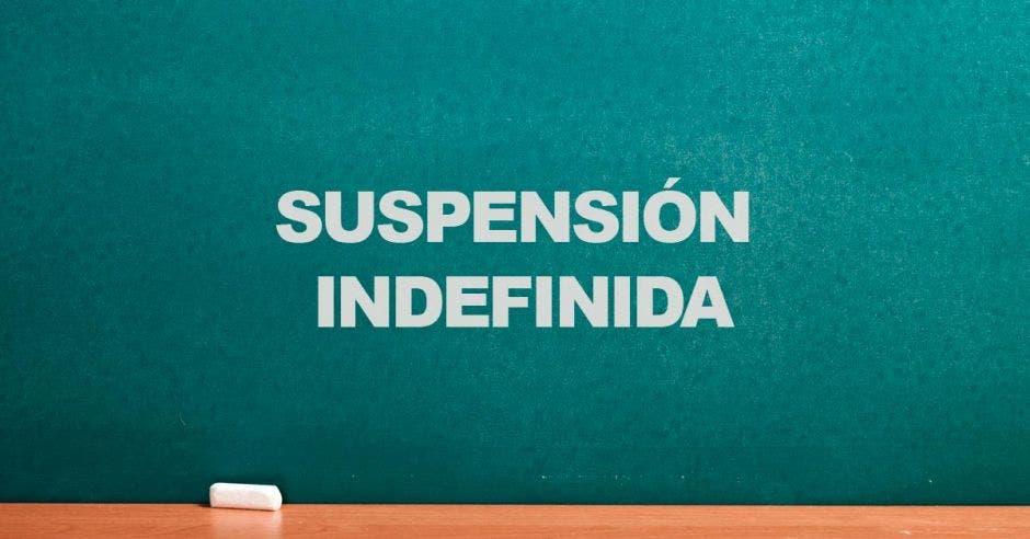 Una pizarra y la palabra suspensión indefinida