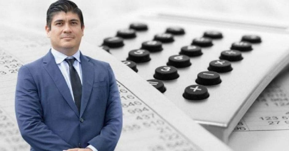 Carlos Alvarado de traje frente a calculadora