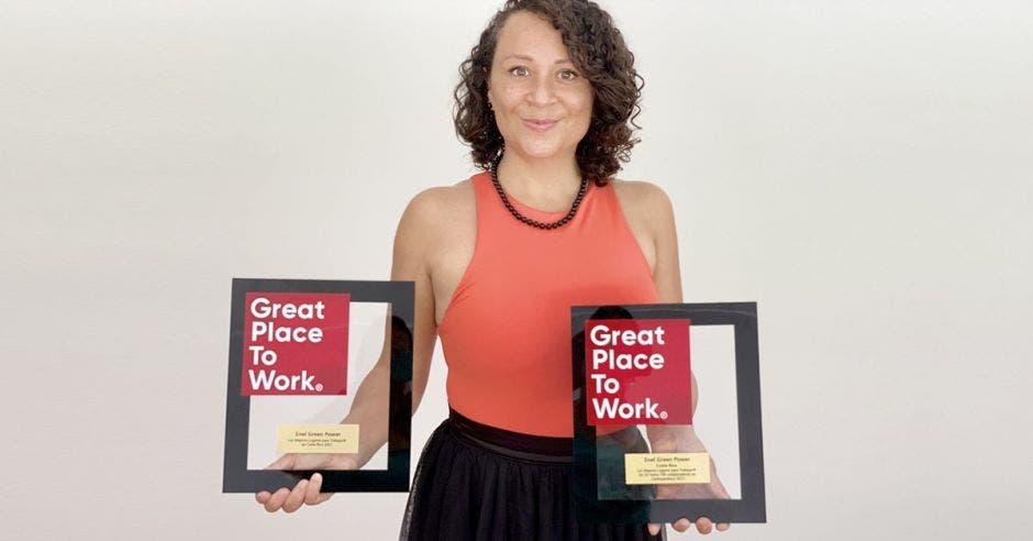 una mujer de pelo rizado, camisa durazno y enagua negra sostiene dos premios forrados con vidrio