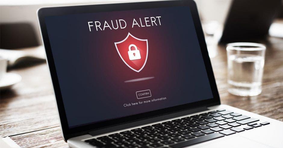 laptop con aviso de alerta de fraude en la pantalla