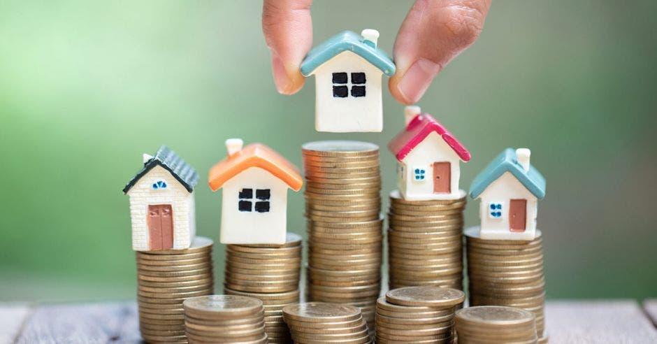 Monedas en columnas y casas miniatura