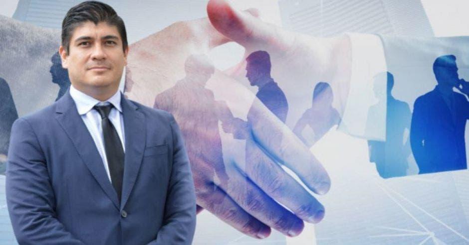 Carlos Alvarado en primer plano, al fondo se ve una imagen de dos manos estrechándose, como llegando a un acuerdo