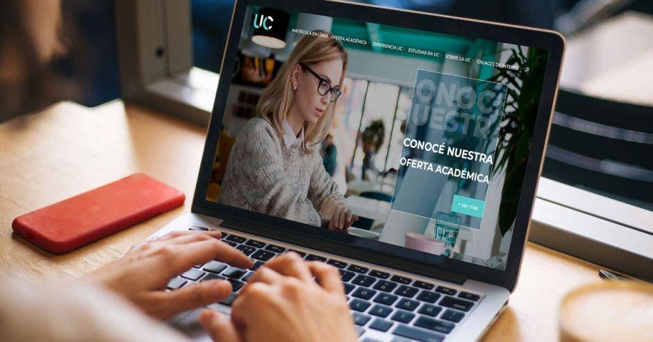 mujer viendo oferta académica de la Universidad Central en laptop