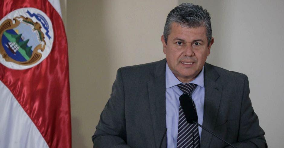 un hombre de saco oscuro y camisa clara, con corbata de rombos