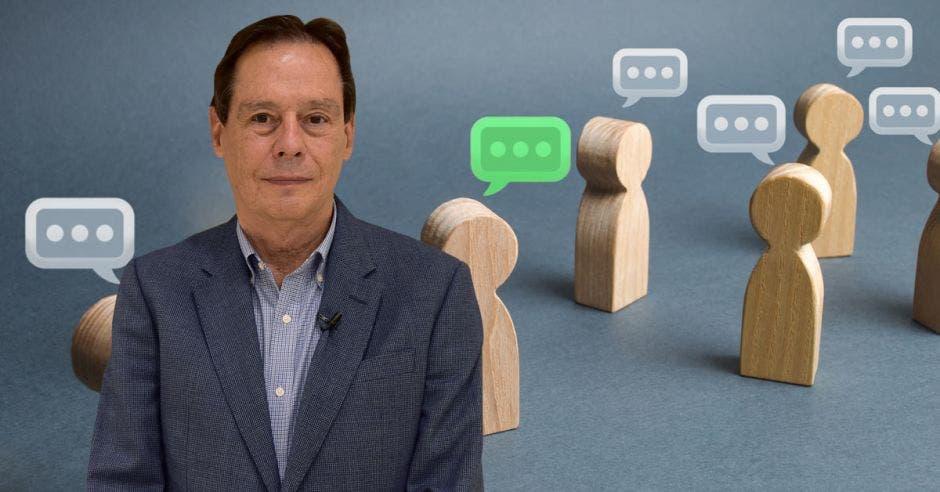 Hombre de traje frente a figuras de madera