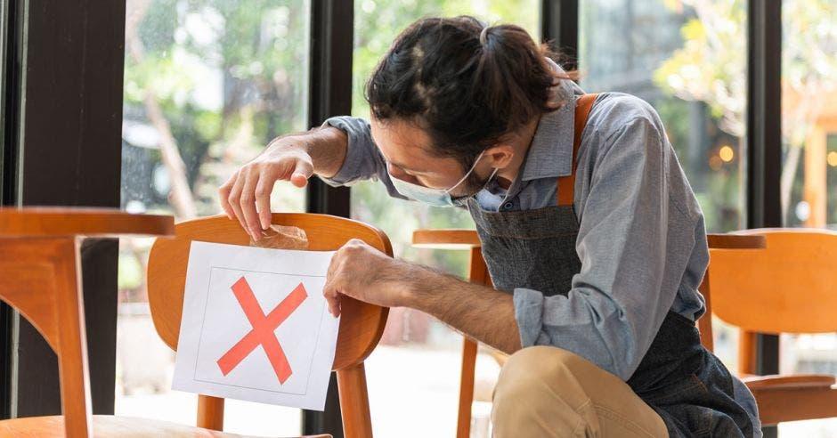 Un camarero asiático pone una señal cruzada en la silla del restaurante o cafetería para hacer distanciamiento social para evitar la propagación del coronavirus