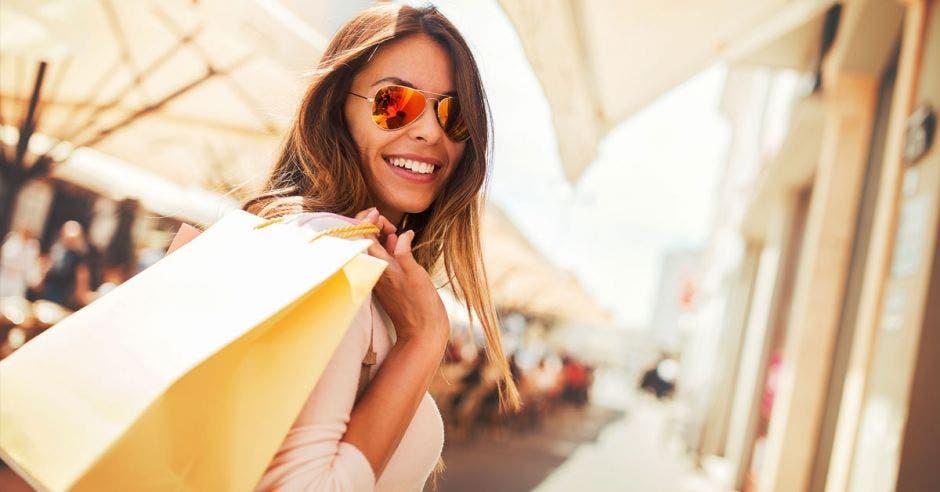 mujer de cabello castaño con lentes de sol, sonriendo y sosteniendo bolsas con la mano sobre el hombro