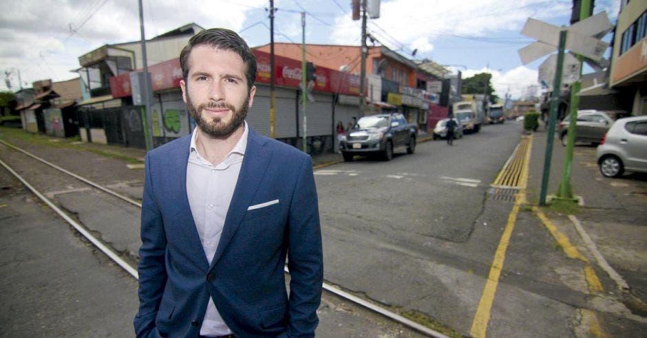 un hombre blanco de barba con camisa blanca y saco azul de pie frente a la línea del tren en una calle de asfalto.