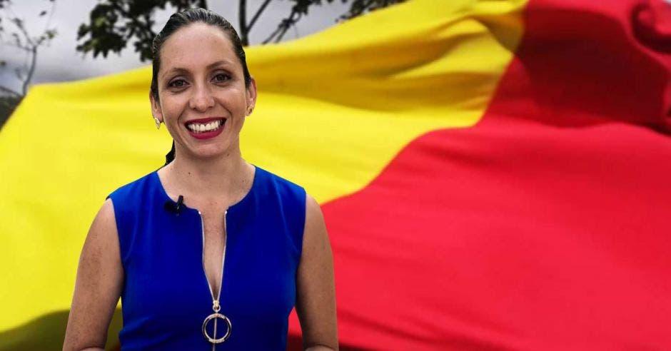 Carolina Hidalgo, precandidata del PAC en primer plano. En segundo plano una bandera del PAC de color rojo y amarillo