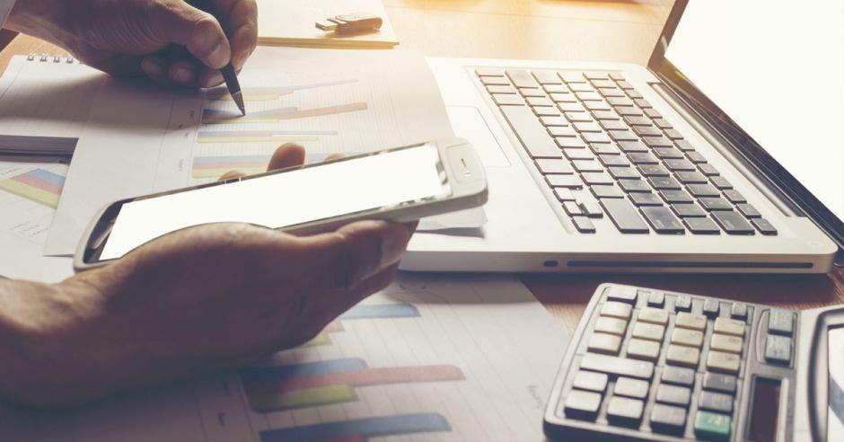 Persona con calculadora, laptop y celular, mientras utiliza bolígrafo
