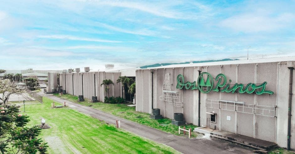 un edificio gris con la palabra Dos Pinos escrita en color verde en su fachada