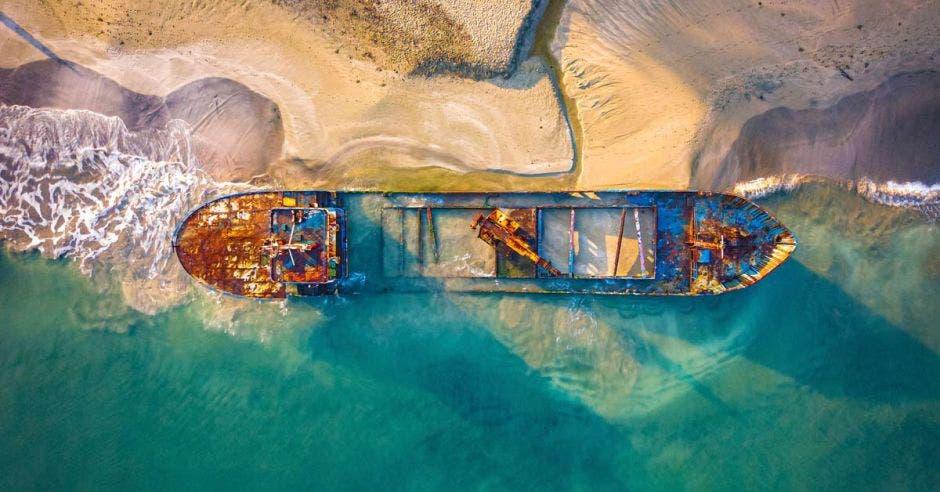 un barco oxidado encallado en una costa
