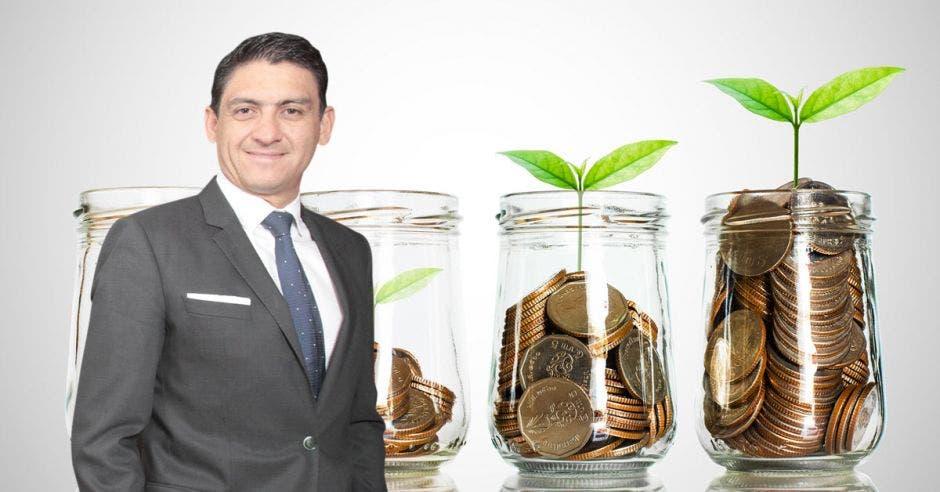 Pedro Beirute, Gerente General de Procomer, de fondo imagen de tarros de cristal con monedas y plantas pequeñas encima