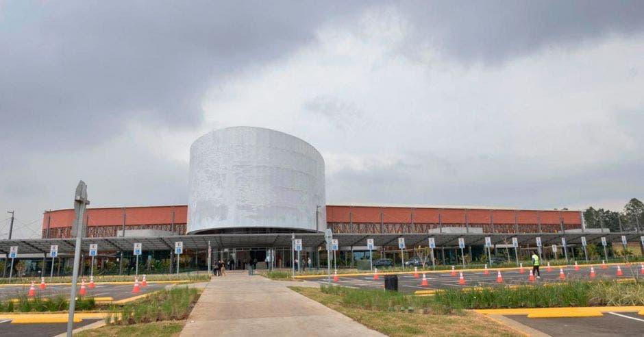 un edificio con una cúpula gris y amplio estacionamiento.