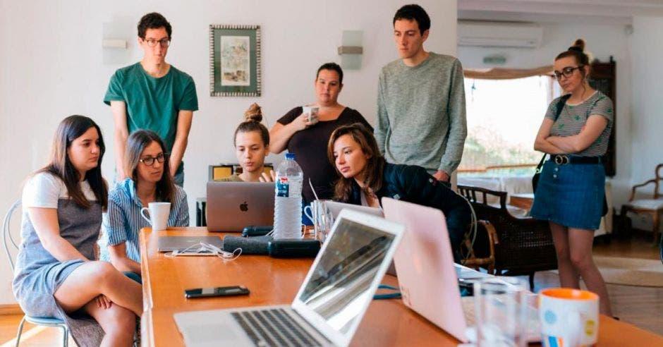 Grupo de trabajo en oficina viendo computadoras