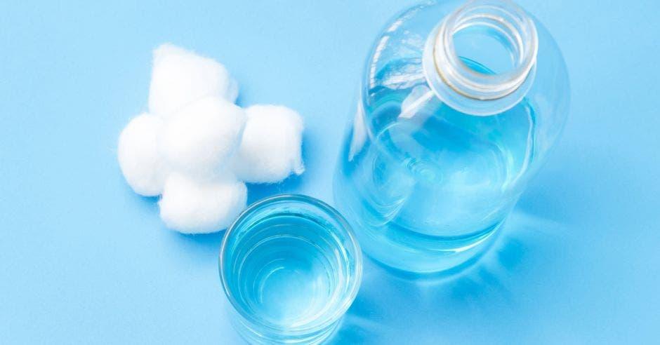 un frasco de alcohol y tres algodones sobre una mesa color celeste