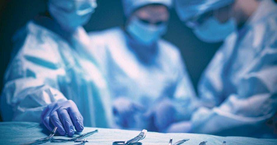 Médicos con mascarilla agarrando implementos