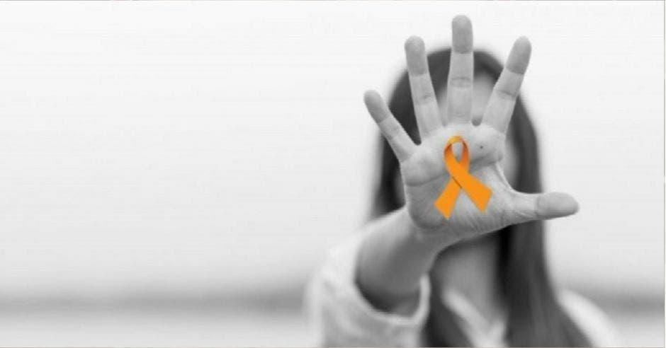 palma de la mano de mujer, en blanco y negro, con listón naranja en el centro
